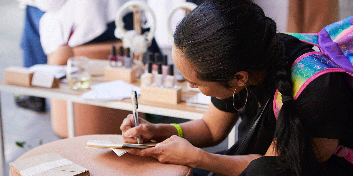 Woman writing a note, woman with dark hair writing, woman writing
