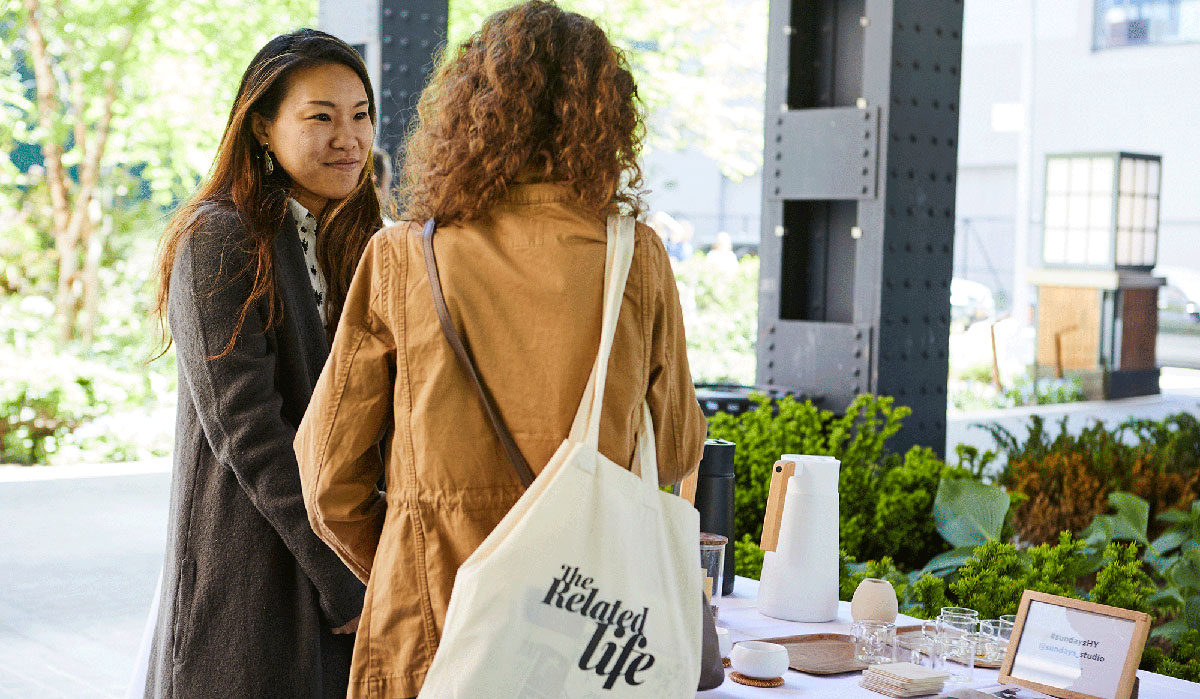 Woman with tote bag, women talking, women in front of table