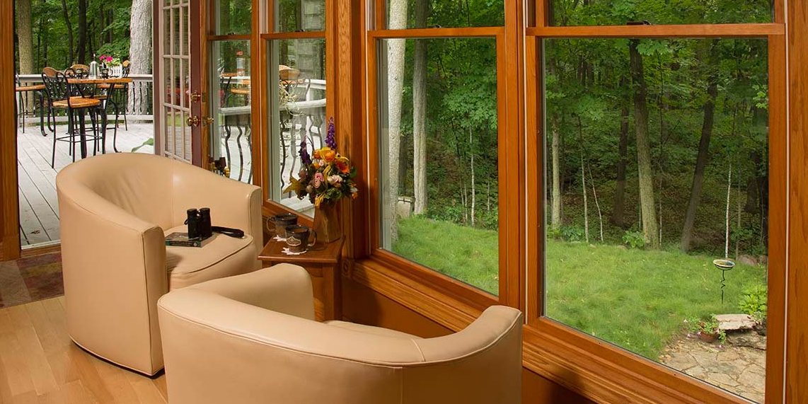 Cabin in woods, chairs looking outside, comfortable chairs in house
