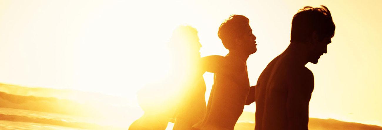 Men running on the beach, sunlight on the beach, surfers