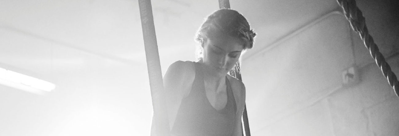 woman exercising, woman doing pull ups, black and white photo of woman exercising