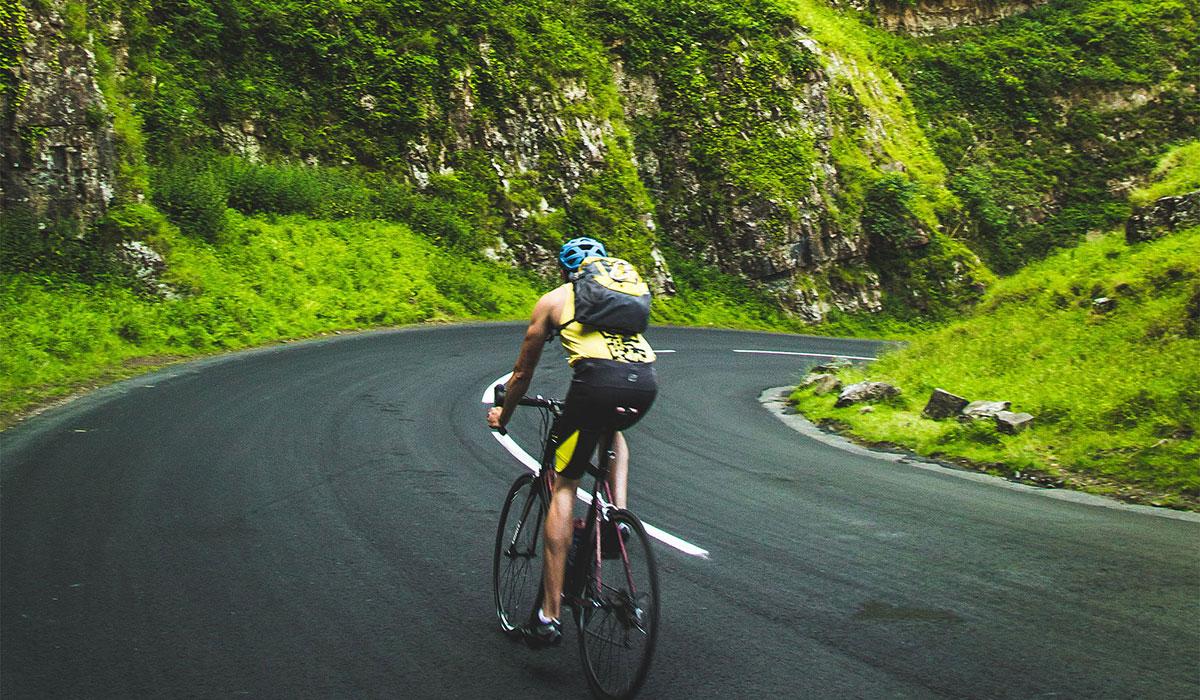 sustainable athlete, man biking in mountains